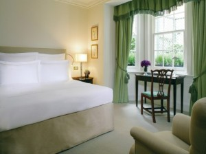 """Appropriately termed """"Duchess Rooms"""" when transformed for female guests, those like this one at the boutique-chic DUKES London Hotel in Mayfair pamper women with women-sized slippers, makeup mirrors, lifestyle magazines, and fresh flowers."""